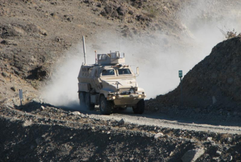 a large, tan off road vehicle driving through rough terrain